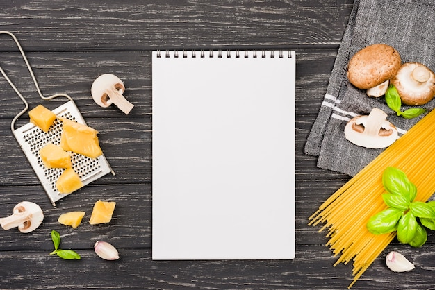 Notebook with ingredients for spaghetti with mushrooms