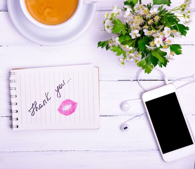 Notebook with an inscription thank you and a kiss from red lipstick