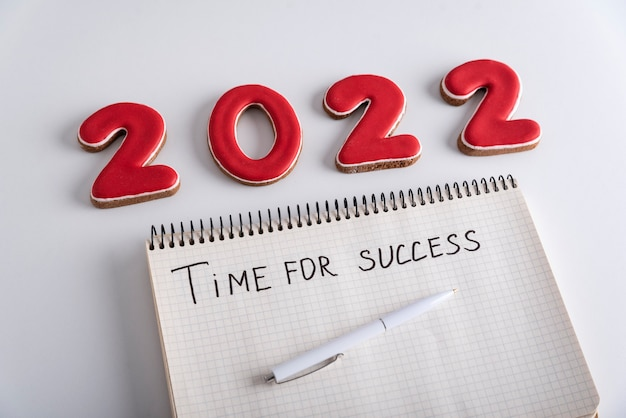 Блокнот с надписью «время успеха», ручка и числа 2022. белый фон.