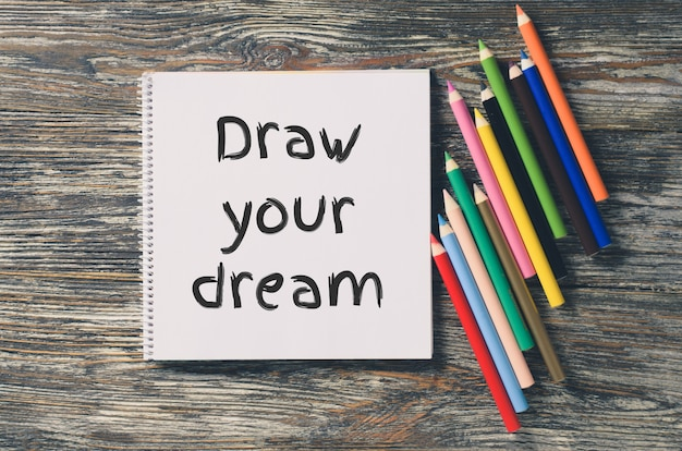 Notebook with inspiration draw your dream and set of colorful pencils.