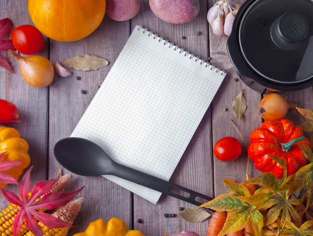 Notebook with kitchen utensils and autumn leaves on the concrete background
