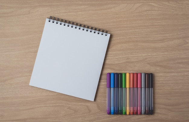 Notebook with many colorful pens on brown wooden table