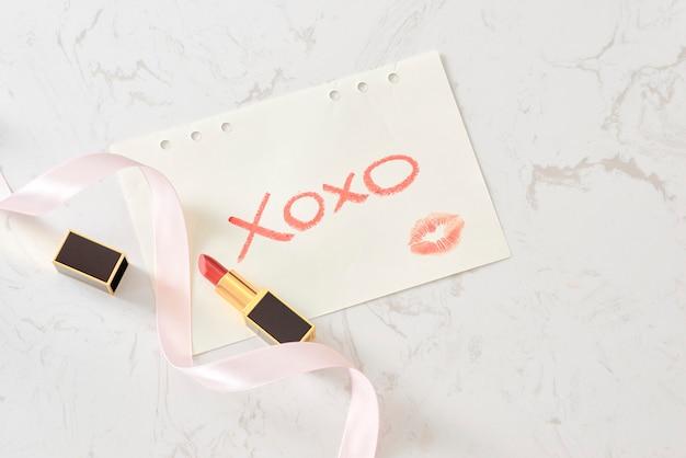 大理石の表面を持つノートブック。 xo xo。グラマースタイル。フラットレイ。赤い唇。