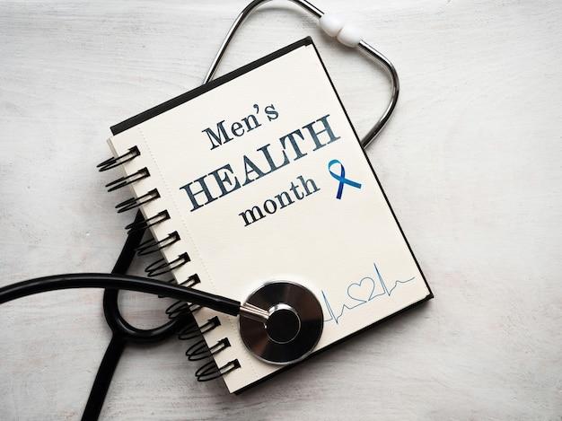 Ноутбук с месяцем мужского здоровья и стетоскопом на белом фоне