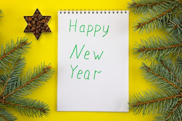 Блокнот с новогодними пожеланиями на фоне еловых веток и орехов.