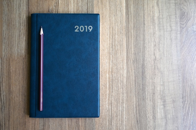 Notebook with number 2019 and pencil on wooden table with copy space for text or product display.