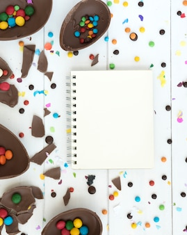 Notebook with open chocolate easter eggs and candies