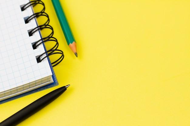 ペンと鉛筆が黄色の背景にノート。