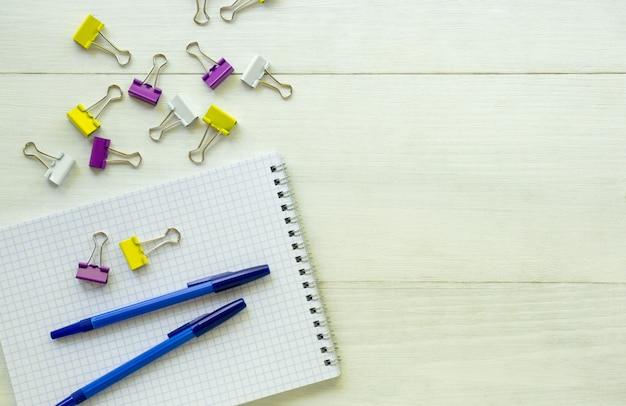 明るい背景にペンと文房具のクリップのノート