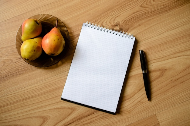 Notebook with pen and apples on a wooden table.