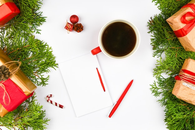 一杯のコーヒーとギフトの横にあるペン付きノート