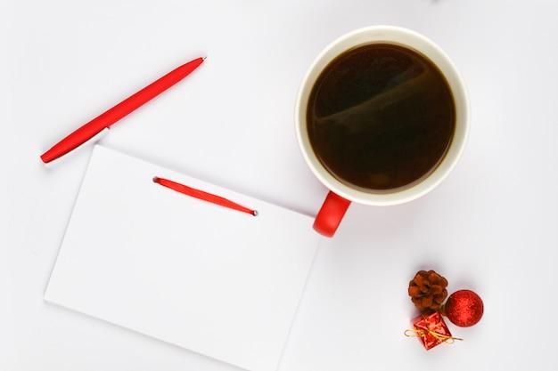 一杯のコーヒーの横にあるペン付きノート