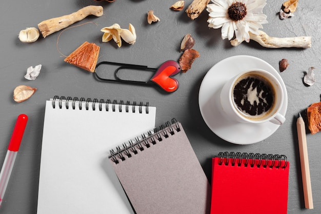 ペン、コーヒー、テーブルの上の花とノート