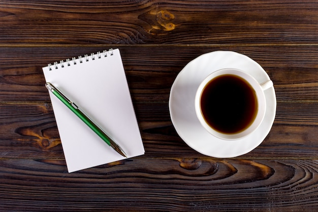 Notebook with pen and coffee cup on wooden background