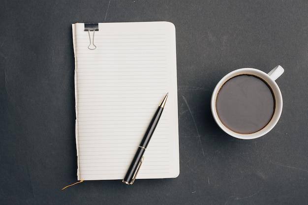 Notebook with pen on dark background and cup of coffee office top view