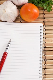 Блокнот с ручкой, чесноком, помидорами и петрушкой на соломенной текстуре