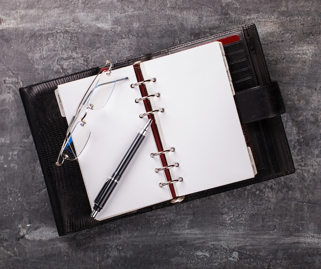 Notebook with pen  glasses business concept