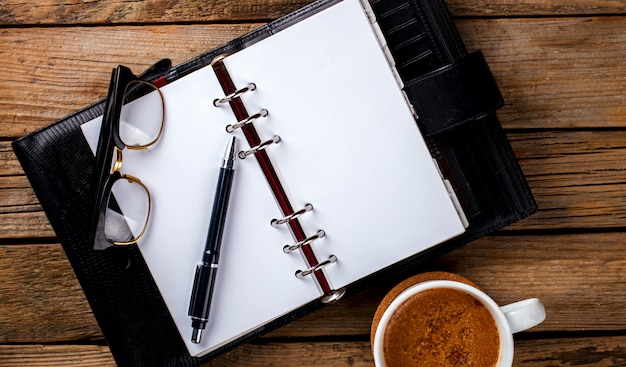 Notebook with pen ,glasses and coffee