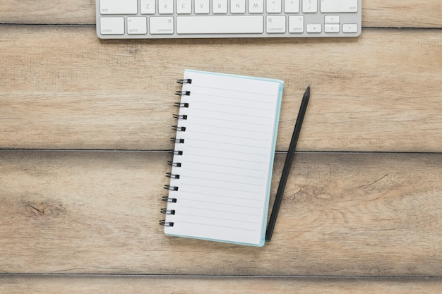 木製のテーブルにキーボードの近くのペンとノート