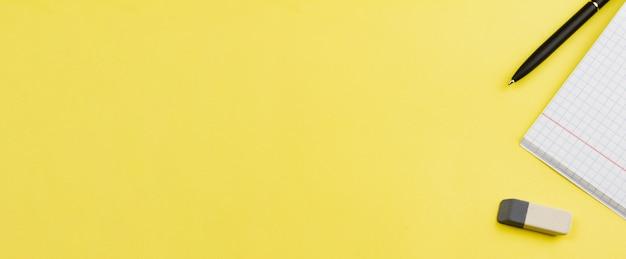 黄色の背景にペンでノートブック。