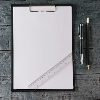 Блокнот с ручкой, карандашом и линейкой на темном деревянном столе