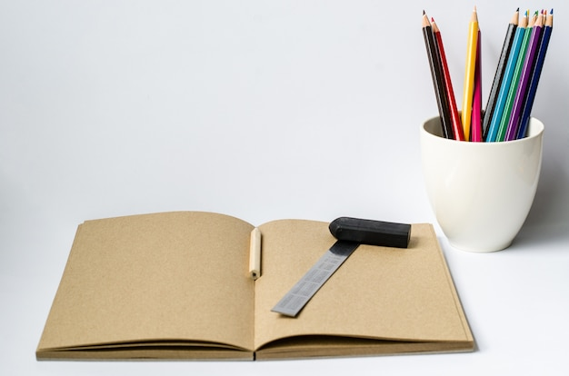Notebook with pencil and black eraser glasses on white background