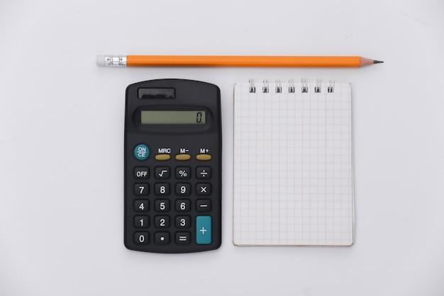 鉛筆、白い背景の上の電卓とノートブック。上面図