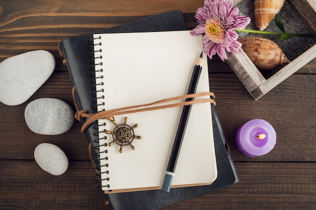Notebook with a pencil and a candle