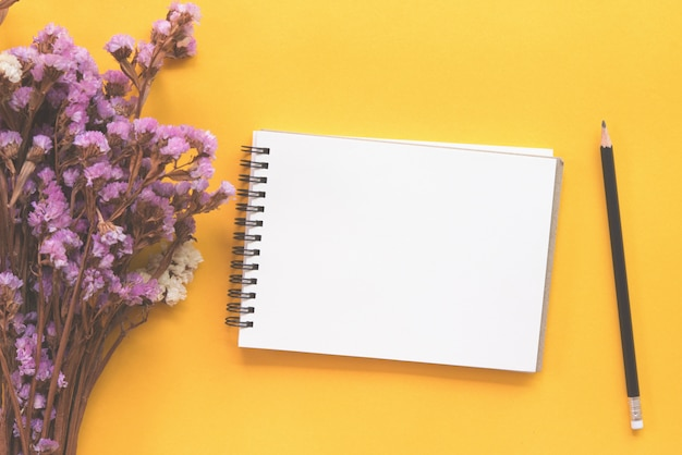 Notebook with pencil and dried flower on yellow background.