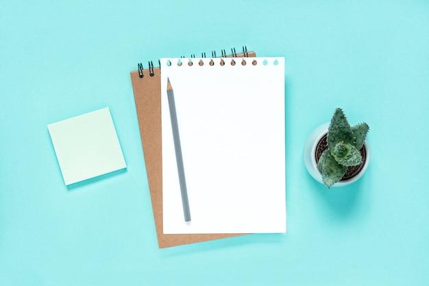 쓰기용 테이블 흰색 페이지에 밝은 파란색 배경 나선형 메모장에 연필이 있는 노트북