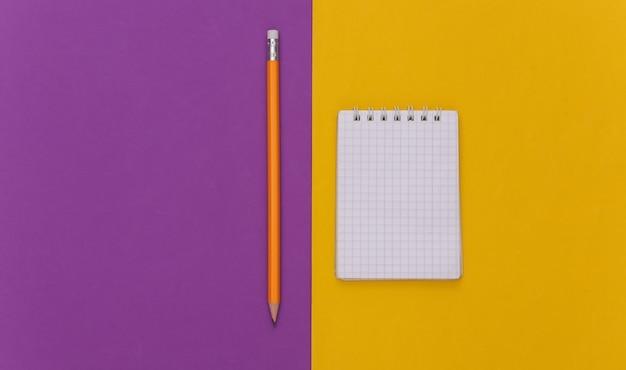 紫黄色の背景に鉛筆でノートブック。上面図