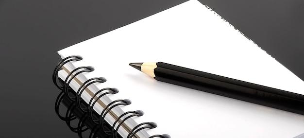 黒の背景に鉛筆でノートブック、コピースペースの上面図