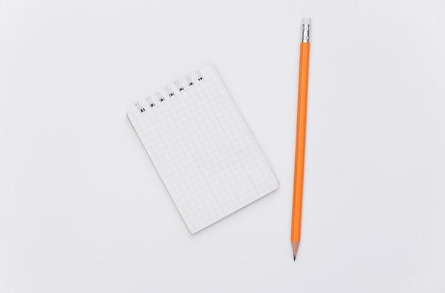 白い背景の上の鉛筆とノートブック。上面図