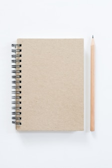Notebook with pencil on white background