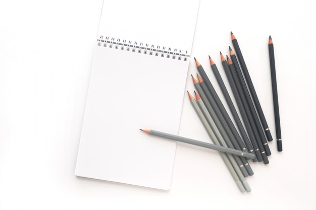Notebook with pencils on white. top view