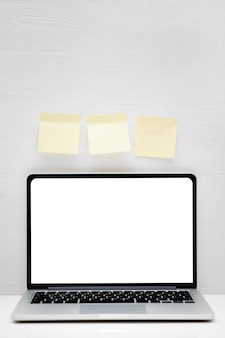 Notebook with place for copy space on a white wooden background with yellow stickers. vertical.