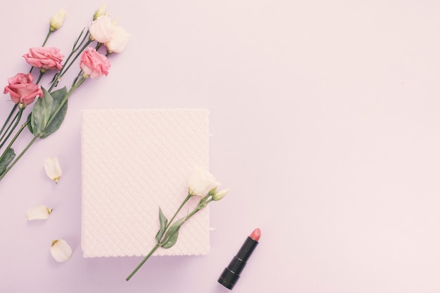 Notebook with rose flowers and lipstick on table
