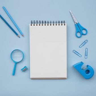Notebook with scissors  magnifying glass pencil sharpener on light blue background