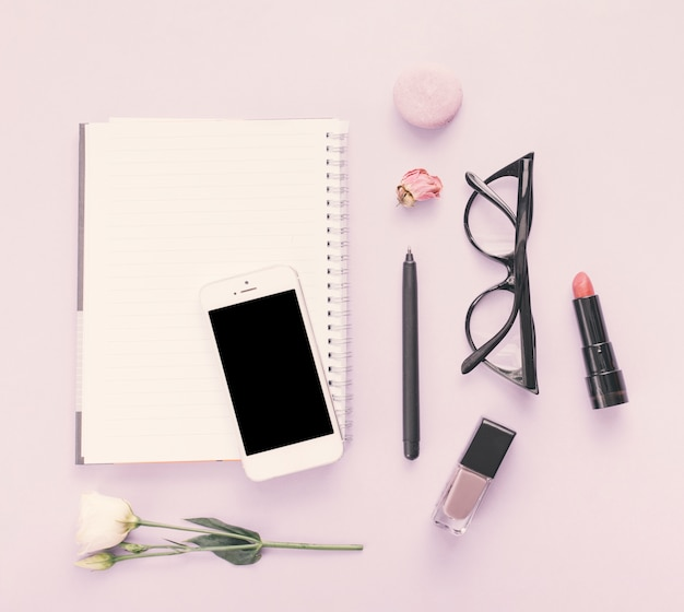 Notebook with smartphone, flower and cosmetics on table