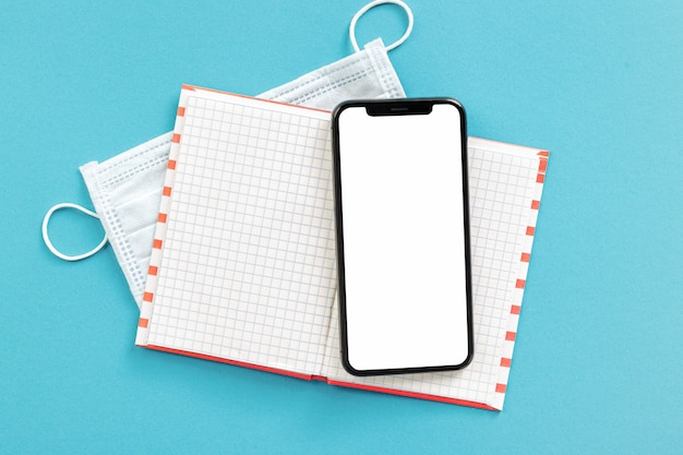 Notebook with smartphone with blank screen and medical face mask on blue background top view remote work concept