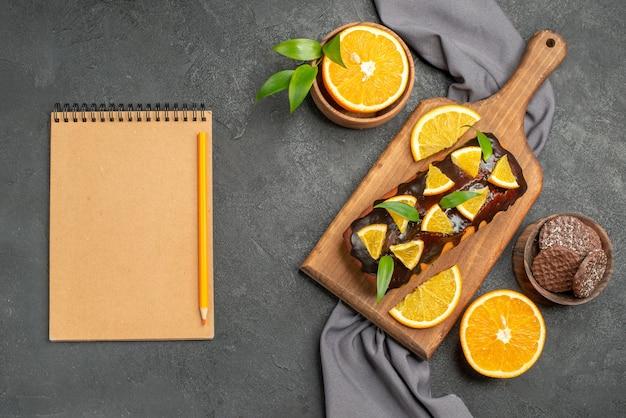 Taccuino con morbide gustose torte tagliate arance con biscotti sul tagliere di legno e asciugamano