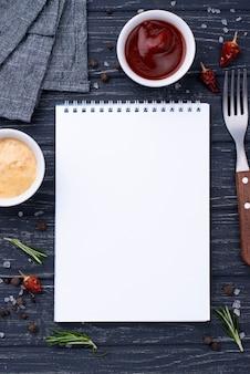 テーブルの上のソースが付いているノート