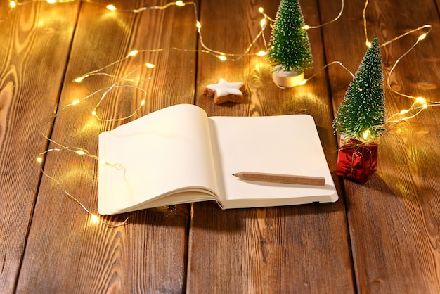 Блокнот с местом для текста на рождественскую тему на деревянном столе