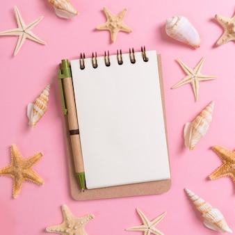 ピンクの背景の上面図フラットレイにsseashellsとノートブック。夏休み、観光、休暇のコンセプトを計画する
