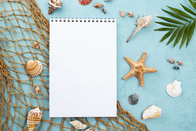 Notebook with starfish beside and shells