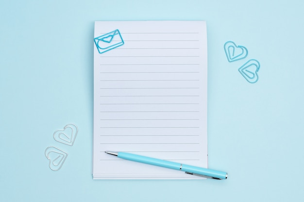 Notebook with stationary items on blue background. paperclips in the shape of heart around the notebook.