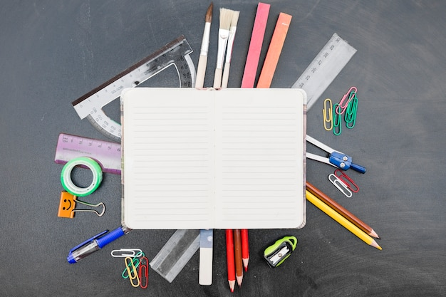 Notebook with stationery on blackboard