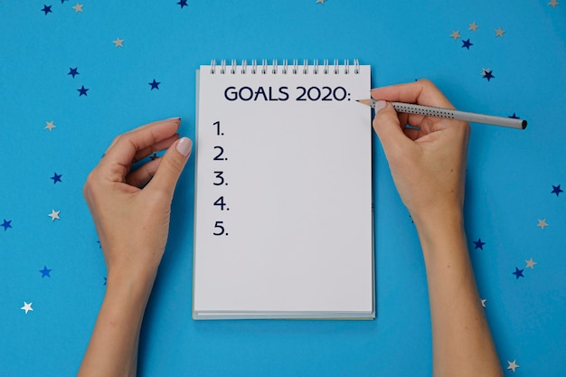 Notebook with text goals 2020 and female hands with pencil