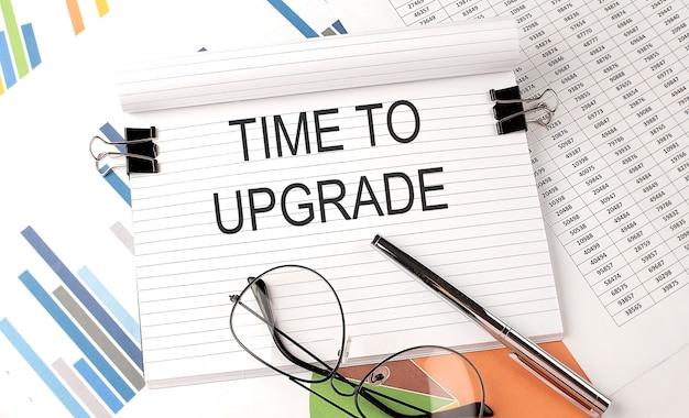 차트, 펜, 안경이 있는 테이블에 ime to upgrade라는 텍스트가 있는 노트북.