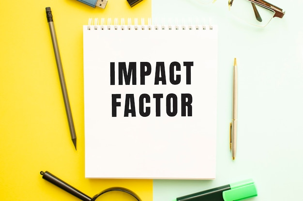 Notebook with text impact factor on office table with office supplies. yellow color background.